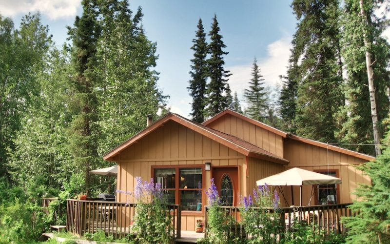 Cabin type house with woods in the background