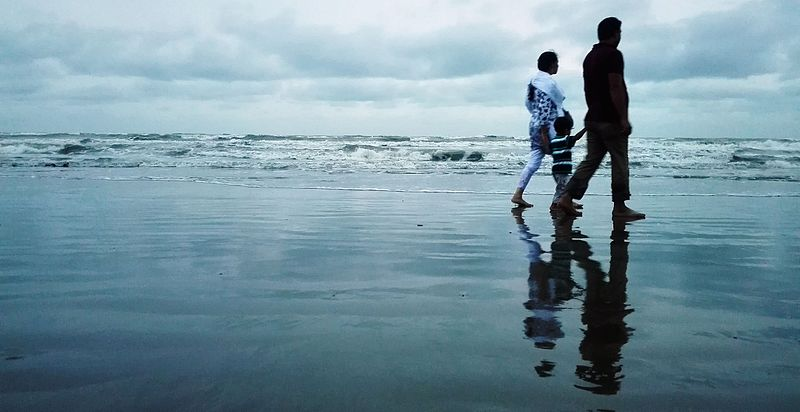A family of three walking on the beach's low tide