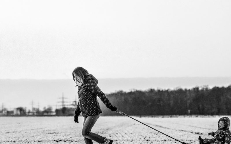A woman pulling a sledge with her child on in the snow