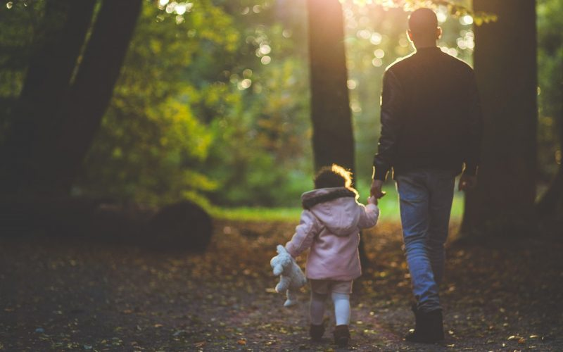 A father and daughter walking the a forrest with the sun shining through the trees