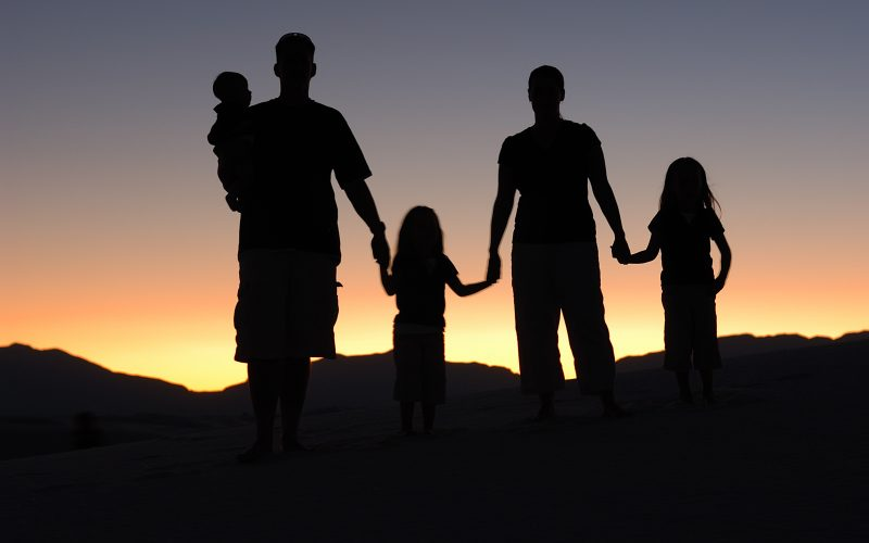 Family holding hands with sunset as backdrop