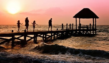 Family walking down a pier next to the sea