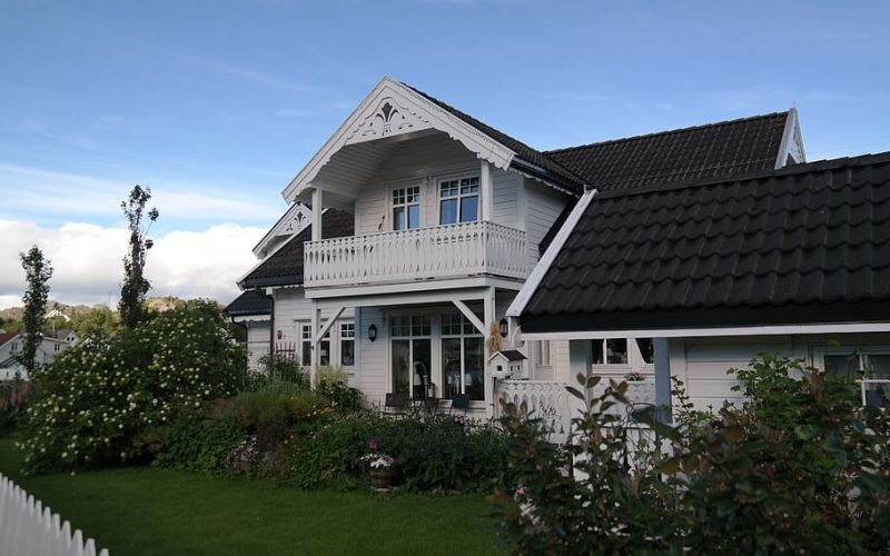 Large lake-house style building with a white picket fence