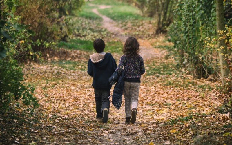 A little boy and girl walking up a path