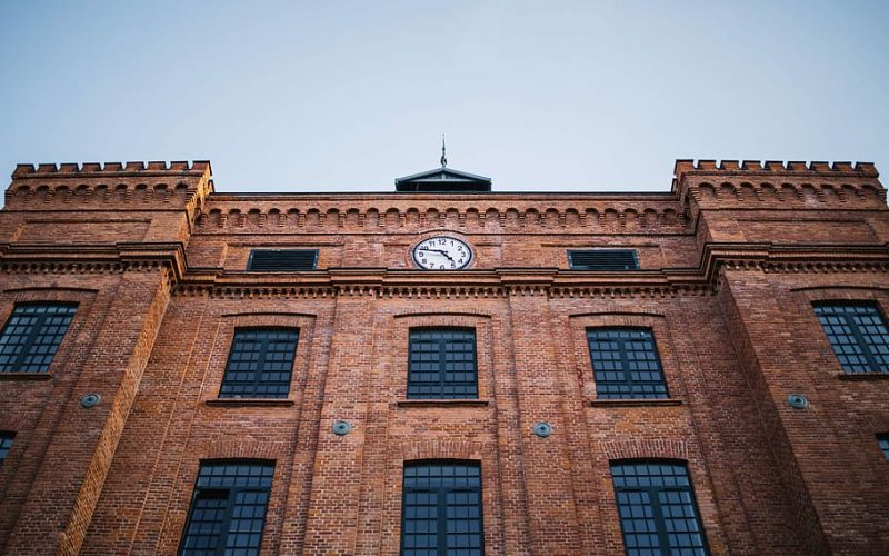 A large building with wide windows and a clock at the top centre