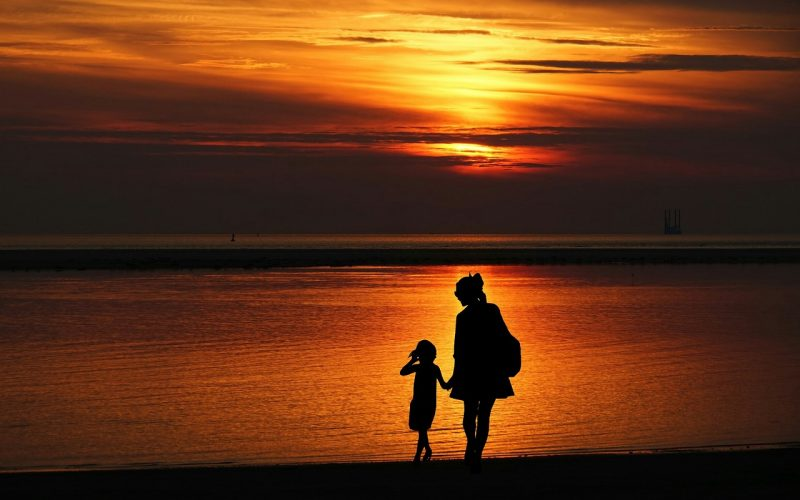 Mother and daughter holding ands by the sea with the sunset in the background