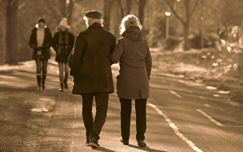 An older couple walking down a path with arms linked together