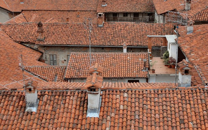 Roof tops of houses in a town all with chimney stacks