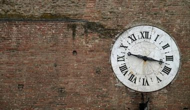 Clock on a wall with roman numerals reading 3:17