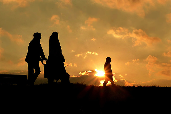Family walking in the meadows with the sun setting