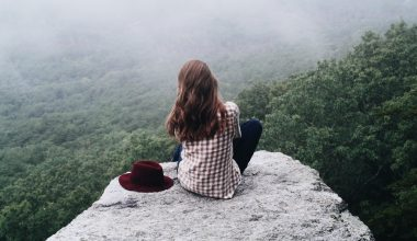 Woman sitting on a cliff side looking out towards a forest below
