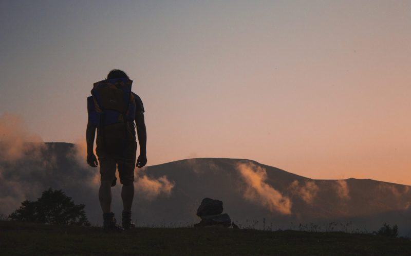 A backpacker walking towards mountains in the far distance