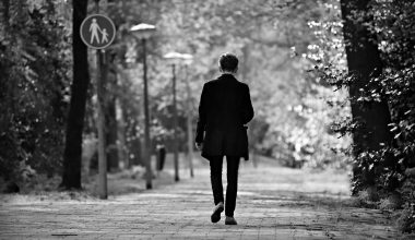 Black and white image of a man walking down a path with lampposts on his left