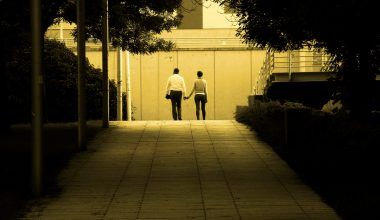 A couple holding hands at the end of a path
