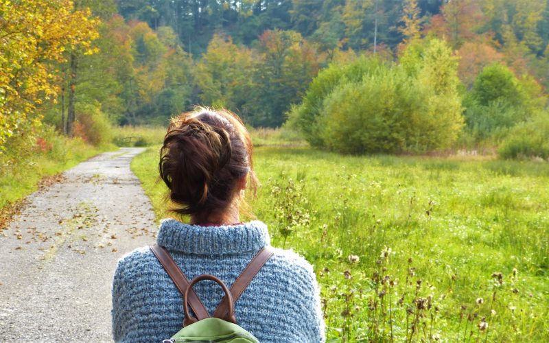 A woman with a green backpack looking at the green scenery