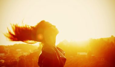 A woman embracing the sun shining down on her