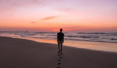 Guy walking on the beach next to the sea with the sun setting