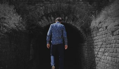 A man walking in a pitch black tunnel