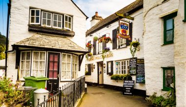 An old style white pub with a tight lane out front
