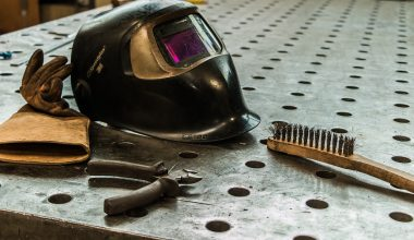 A welding mask and gloves on a work bench
