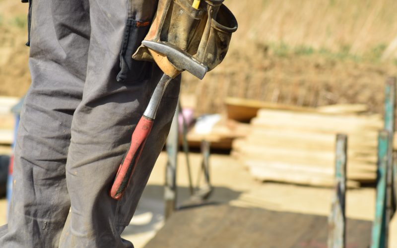 Worker with a hammer in side pocket facing supplies