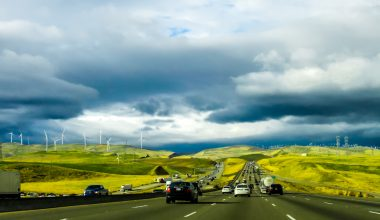 A busy main road with cars driving on wither side with wind turbines in the background