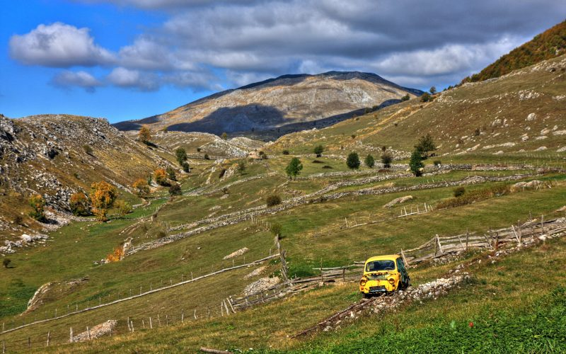 A yellow car in the countryside