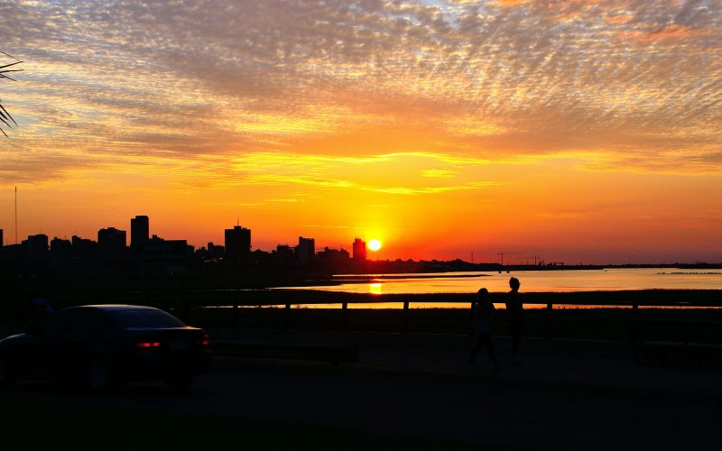 A car parked with the sun setting behind city buildings